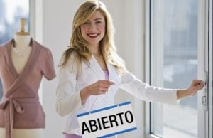 """Woman with a sign that says """"Open"""" in Spanish"""