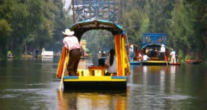 Boatman poling brightly colored boat Xochimilco canals floating gardens Mexico City